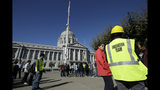 An evacuation team member stands with participants during an earthquake preparedness drill across the street from City Hall in San Francisco, Thursday, Oct. 17, 2019. Earthquake early warning alerts will become publicly available throughout California for the first time this week, potentially giving people time to protect themselves from harm, the Governor's Office of Emergency Services said Wednesday. (AP Photo/Jeff Chiu)