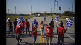 ARCHIVO - En esta fotografía de archivo del 16 de septiembre de 2019, varios trabajadores huelguistas obstruyen el paso a dos camiones de carga afuera de la planta de ensamble de General Motors en Bowling Green, Kentucky. (AP Foto/Bryan Woolston, Archivo)