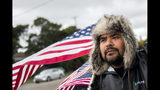 """Michael Perez, 48 of Saginaw, stand with waving American flags to show solidarity alongside other General Motors' Flint Assembly Plant employees and UAW members, who line the street with picket signs on the 31st day of the nationwide UAW strike against GM after stalled contract negotiations on Wednesday, Oct. 16, 2019, outside of the Flint Assembly Plant in Flint, Mich. Perez has been employed as an electrician in the body shop for more than 10 years. ÒWe get to keep our job and our health insurance, but we're mainly fighting for the younger crowd and the future of this plant,"""" Perez said. (Jake May/The Flint Journal via AP)"""