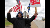 Bill Jackson, of St. Louis, gives a thumbs up to drivers that wave or honk as United Auto Workers outside the GM Wentzville Assembly Center in Wentzville, Mo., Wednesday, Oct. 16, 2019. UAW workers have been on strike since Sept. 16, but have reached a tentative deal with GM today. Workers expressed cautious optimism, but will likely remain on the picket line until an official deal has been reached. (Cristina M. Fletes/St. Louis Post-Dispatch via AP)