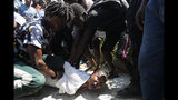 During a funeral for two people killed in violence related to recent protests, mourners restrain a woman related to one of the victims after she went into a trance at Champ de Mars park near the National Palace in Port-au-Prince, Haiti, Wednesday, Oct. 16, 2019. Funerals for 11 of at least 20 people killed were held in six cities, including the capital of Port-au-Prince, where at least two people were injured in a protest that broke out when presidential guards tried to block a road near where hundreds had gathered around the coffins of two victims. (AP Photo/Rebecca Blackwell)
