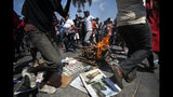People jog around a fire during a voodoo ceremony to grant protection to the people, as protesters calling for the resignation of President Jovenel Moise gathered at a bridge in the Delmar area of Port-au-Prince, Haiti, Thursday, Oct. 17, 2019. Haiti's embattled president was forced on Thursday to hold a private ceremony amid heavy security for what is usually a public celebration of one of the country's founding fathers, revolution leader Jean-Jacques Dessalines. (AP Photo/Rebecca Blackwell)