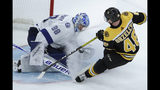 Tampa Bay Lightning goaltender Andrei Vasilevskiy (88) makes a save against Boston Bruins defenseman Matt Grzelcyk (48) in overtime of an NHL hockey game Thursday, Oct. 17, 2019, in Boston. The Lightning won 4-3 in a shootout. (AP Photo/Elise Amendola)