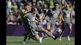 Minnesota United midfielder Kevin Molino, second from left, gets to a ball in front of Seattle Sounders forward Nicolas Lodeiro, left, during the first half of an MLS soccer match, Sunday, Oct. 6, 2019, in Seattle. The Sounders won 1-0. (AP Photo/Ted S. Warren)