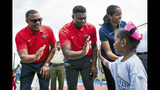 In this June 22, 2019, photo, New Orleans Pelicans head coach Alvin Gentry, left, draft pick Zion Williamson, and vice president of operations Swin Cash greet children before a ribbon cutting ceremony at the refurbished basketball court at Goretti Playground in New Orleans. Cash believes the NBA is realizing having more women is important to growing the league's overall brand, business and bottom line. (Shawn Fink/The Advocate via AP)