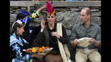 In this photo released by Press Information Department, Mmembers of Kalash community greet Britain's Prince William, center, and his wife Kate with traditional caps during their visit to Bumburate Valley, an area of Pakistan's northern Chitral district, Wednesday Oct. 16, 2019. Britain's Prince William and wife Kate traveled to Pakistan's scenic northern mountains and glaciers, drawing attention to the challenges of climate change in the South Asian nation, where glaciers are melting at a fast pace. (Press Information Department via AP)