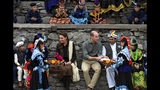 In this photo released by Press Information Department, Members of Kalash community greet Britain's Prince William, center, and his wife Kate to presents and traditional caps during their visit to Bumburate Valley, an area of Pakistan's northern Chitral district, Wednesday Oct. 16, 2019. (Press Information Department via AP)