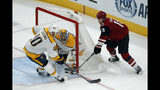 Nashville Predators goaltender Juuse Saros makes the save on a shot by Arizona Coyotes left wing Christian Dvorak (18) as Colton Sissons (10) defends in the first period during an NHL hockey game, Thursday, Oct. 17, 2019, in Glendale, Ariz. (AP Photo/Rick Scuteri)