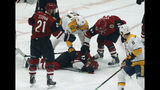 Arizona Coyotes defenseman Jordan Oesterle (82) lies on the ice after getting hit with the puck as Derek Stepan (21), Phil Kessel (81) and Nashville Predators left wing Austin Watson (51) try to help him in the first period during an NHL hockey game, Thursday, Oct. 17, 2019, in Glendale, Ariz. (AP Photo/Rick Scuteri)