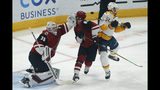 Arizona Coyotes defenseman Jordan Oesterle (82) is hit in the back of the head with a puck in front of goaltender Darcy Kuemper (35) as Nashville Predators left wing Austin Watson (51) tries to avoid the hit in the first period during an NHL hockey game, Thursday, Oct. 17, 2019, in Glendale, Ariz. (AP Photo/Rick Scuteri)