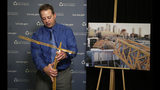 Brian Haight, crane program manager for Washington state's Department of Labor and Industries, uses a model of a crane to explain how a crane can become unstable after pins are removed and high winds come up as he talks about a crane collapse in Seattle months earlier that killed four, Thursday, Oct. 17, 2019, in Tukwila, Wash. The photo behind him shows broken off sections from the collapse. Washington state's L&I released the results of its investigation on the collapse Thursday. It found, as experts have long suspected, that the crane toppled because workers who were disassembling it had prematurely removed pins securing the sections of the crane's mast. (AP Photo/Elaine Thompson)