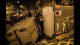 Demonstrators take shelter behind a barricade during clashes with police in Barcelona, Spain, Wednesday, Oct. 16, 2019. Spain's government said Wednesday it would do whatever it takes to stamp out violence in Catalonia, where clashes between regional independence supporters and police have injured more than 200 people in two days. (AP Photo/Bernat Armangue)