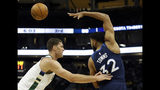 Minnesota Timberwolves' Karl-Anthony Towns (32) passes behind his back against Milwaukee Bucks' Brook Lopez during the second half of a preseason NBA basketball game Thursday, Oct. 17, 2019, in Milwaukee. (AP Photo/Aaron Gash)