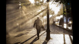 A pedestrian quickens his pace to escape the fumes caused by tear gas tear launched by police during a protest against the rising cost of subway and bus fares, in Santiago, Friday, Oct. 18, 2019. (AP Photo/Esteban Felix)