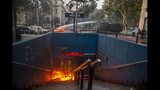 A police water cannon puts out a burning barricade near the Santa Lucia subway station during a protest against the rising cost of subway and bus fares, in Santiago, Friday, Oct. 18, 2019. (AP Photo/Esteban Felix)