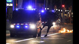 A protestor kicks a police van during clashes in Barcelona, Spain, Thursday, Oct. 17, 2019. Catalonia's separatist leader vowed Thursday to hold a new vote to secede from Spain in less than two years as the embattled northeastern region grapples with a wave of violence that has tarnished a movement proud of its peaceful activism. (AP Photo/Emilio Morenatti)
