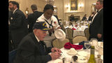 In this June 3, 2018, photo, provided by John W. (Jack) Crawford III, retired Navy Capt. Jack Crawford signs an autograph at the Battle of Midway dinner at the Army-Navy Club in Arlington, Va. Crawford, who recently turned 100 years old, served on the USS Yorktown during the World War II Battle of Midway and survived the Yorktown's sinking. (John W. (Jack) Crawford III via AP)