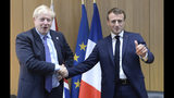Britain's Prime Minister Boris Johnson poses with French President Emmanuel Macron, right, during a European Union leaders summit in Brussels, Belgium, Thursday Oct. 17, 2019. Britain and the European Union reached a new tentative Brexit deal on Thursday, hoping to finally escape the acrimony, divisions and frustration of their three-year negotiation. (Johanna Geron/Pool via AP)