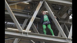 A climate protester walks along a beam after climbing up onto the scaffolding surrounding the Elizabeth Tower that houses the Big Ben clock in London, Friday, Oct. 18, 2019. (AP Photo/Kirsty Wigglesworth)