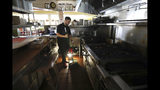 FILE - In this Oct. 10, 2019, file photo, Salvador Espinosa sweeps in the kitchen of a Mary's Pizza Shack restaurant during a Pacific Gas and Electric Co. power shutdown in Santa Rosa, Calif. California's largest utility pledged to improve communications. But it reminded state regulators that its difficult decision to pre-emptively shut off power to more than 2 million people last week may have prevented deadly wildfires. (Christopher Chung/The Press Democrat via AP, File)