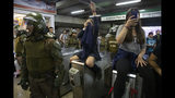 Chile's Carabineros stand next to students blocking the turnstile to the subway protesting against the rising cost of subway and bus fare, in Santiago, Friday, Oct. 18, 2019. (AP Photo/Esteban Felix)