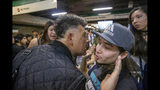 A man argues forcibly with a student who is blocking the turnstile to the subway as a protest against the rising cost of subway and bus fare, in Santiago, Friday, Oct. 18, 2019. The man had paid his subway ticket and wanted to get through the students blocking he way. (AP Photo/Esteban Felix)