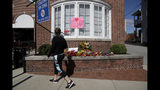 A woman looks at flowers and messages outside of the office of the late U.S. Rep. Elijah Cummings, D-Md., a day after the congressman died Friday, Oct. 18, 2019, in Catonsville, Md. Many faith leaders, activists and politicians in Baltimore have one thing in common: They were mentored by Cummings. Cummings, who died at 68, inspired and advised others, sharing his political wisdom. (AP Photo/Julio Cortez)
