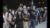 Protesters wear masks and hold up their mobile phone lights in Hong Kong, Friday, Oct. 18, 2019. Hong Kong pro-democracy protesters are donning cartoon/superheroes masks as they formed a human chain across the semiautonomous Chinese city, in defiance of a government ban on face coverings. (AP Photo/Kin Cheung)