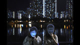 Protesters wear masks of Chinese President Xi Jinping, right, and Hong Kong Chief Executive Carrie Lam during a protest in Hong Kong, Friday, Oct. 18, 2019. Hong Kong pro-democracy protesters are donning cartoon/superhero masks as they formed a human chain across the semiautonomous Chinese city, in defiance of a government ban on face coverings. (AP Photo/Vincent You)