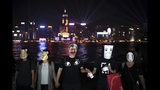 A protester wearing a mask depiting Chinese President Xi Jinping attends a protest with others in Hong Kong, Friday, Oct. 18, 2019. Hong Kong pro-democracy protesters are donning cartoon/superhero masks as they formed a human chain across the semiautonomous Chinese city, in defiance of a government ban on face coverings. (AP Photo/Felipe Dana)