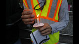 A worker holds a candle during a candlelight vigil outside city hall for deceased and injured workers from the Hard Rock Hotel construction collapse Sat., Oct., 12, in New Orleans, Thursday, Oct. 17, 2019. The vigil was organized by various area labor groups. (AP Photo/Gerald Herbert)