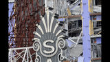 The Saenger Theater sign is seen in the foreground of the damaged Hard Rock Hotel, Thursday, Oct. 17, 2019, in New Orleans. The 18-story hotel project that was under construction collapsed last Saturday, killing three workers. Two bodies remain in the wreckage. (AP Photo/Gerald Herbert)