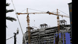 Two unstable cranes loom over the construction of a Hard Rock Hotel, Thursday, Oct. 17, 2019, in New Orleans. The 18-story hotel project that was under construction collapsed last Saturday, killing three workers. Two bodies remain in the wreckage. Authorities say explosives will be strategically placed on the two unstable construction cranes in hopes of bringing them down with a series of small controlled blasts ahead of approaching tropical weather. (AP Photo/Gerald Herbert)