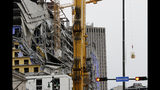 Workers in a bucket, right, begin the process of planting explosive charges on two unstable cranes at the Hard Rock Hotel, which underwent a partial, major collapse on Saturday, Oct. 12, in New Orleans, viewed on Thursday, Oct. 17, 2019. Authorities say explosives will be strategically placed on the two unstable construction cranes in hopes of bringing them down with a series of small controlled blasts ahead of approaching tropical weather. Officials hope to bring the towers down Friday without damaging nearby businesses and historic buildings in and around the nearby French Quarter. (AP Photo/Gerald Herbert)
