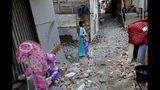 In this Tuesday. Oct. 15, 2019, photo, a girl walks on an alley in a slum in Jakarta, Indonesia. Known for his down-to-earth style with a reputation for clean governance, Indonesian President Joko Widodo's signature policy has been improving Indonesia's inadequate infrastructure and reducing poverty, which afflicts close to a tenth of Indonesia's nearly 270 million people. But raising money would be harder at a time of global economic slowdown, major trade conflicts and falling exports. (AP Photo/Tatan Syuflana)