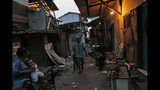 In this Tuesday. Oct. 15, 2019, photo, a man walks on an alley at a slum in Jakarta, Indonesia. Known for his down-to-earth style with a reputation for clean governance, Indonesian President Joko Widodo's signature policy has been improving Indonesia's inadequate infrastructure and reducing poverty, which afflicts close to a tenth of Indonesia's nearly 270 million people. But raising money would be harder at a time of global economic slowdown, major trade conflicts and falling exports. (AP Photo/Tatan Syuflana)