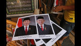 In this Wednesday. Oct. 16, 2019, photo, portraits of Indonesian President Joko Widodo, left, and Vice President-elect Ma'ruf Amin are displayed at a stall in Jakarta, Indonesia. Known for his down-to-earth style with a reputation for clean governance, Widodo's signature policy has been improving Indonesia's inadequate infrastructure and reducing poverty, which afflicts close to a tenth of Indonesia's nearly 270 million people. But raising money would be harder at a time of global economic slowdown, major trade conflicts and falling exports. (AP Photo/Tatan Syuflana)