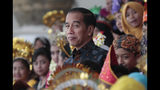 In this Oct. 7, 2019, photo, Indonesian President Joko Widodo reacts as he walks past Indonesian children in traditional dresses during an event at the presidential palace in Bogor, Indonesia. Known for his down-to-earth style with a reputation for clean governance, Widodo's signature policy has been improving Indonesia's inadequate infrastructure and reducing poverty, which afflicts close to a tenth of Indonesia's nearly 270 million people. But raising money would be harder at a time of global economic slowdown, major trade conflicts and falling exports. (AP Photo/Dita Alangkara)