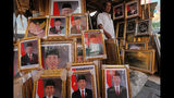 In this Wednesday. Oct. 16, 2019, photo, a man walks past portraits of Indonesian President Joko Widodo and Vice President-elect Ma'ruf Amin displayed at a stall in Jakarta, Indonesia. Known for his down-to-earth style with a reputation for clean governance, Widodo's signature policy has been improving Indonesia's inadequate infrastructure and reducing poverty, which afflicts close to a tenth of Indonesia's nearly 270 million people. But raising money would be harder at a time of global economic slowdown, major trade conflicts and falling exports. (AP Photo/Tatan Syuflana)