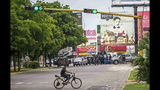 """Unidentified gunmen block a street in Culiacan, Mexico, Thursday, Oct. 17, 2019. An intense gunfight with heavy weapons and burning vehicles blocking roads raged in the capital of Mexico's Sinaloa state Thursday after security forces located one of Joaquín """"El Chapo"""" Guzmán's sons who is wanted in the U.S. on drug trafficking charges. (AP Photo/Augusto Zurita)"""