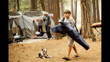 FILE - In this July 25, 2018, file photo, River Martinez, 10, breaks camp at the Upper Pines Campground in Yosemite National Park, Calif. The Interior Department is considering recommendations to modernize campgrounds within the National Park Service. (AP Photo/Noah Berger, File)