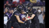 Northwestern quarterback Aidan Smith, right, hands off to running back Isaiah Bowser during the first half of an NCAA college football game against Ohio State, Friday, Oct. 18, 2019, in Evanston, Ill. (AP Photo/Charles Rex Arbogast)