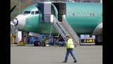 FILE - In this April 26, 2019, file photo a worker walks past a Boeing 737 MAX 8 airplane being built for Oman Air at Boeing's assembly facility in Renton, Wash. Passengers who refuse to fly on a Boeing Max won't be entitled to compensation if they cancel. However, travel experts think airlines will be very flexible in rebooking passengers of giving them refunds if they're afraid to fly on a plane that has crashed twice. (AP Photo/Ted S. Warren, File)