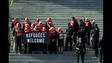 FILE - In this Oct. 15, 2019 file photo, faith leaders and members of human rights groups wearing a life vests symbolizing the life-saving program are arrested during a protest calling congress not to end refugee resettlement program, at the steps of the U.S. Capitol in Washington. The Turkish assault on northern Syria in the wake of President Donald Trump's troop withdrawal from the region has jeopardized a goal often spotlighted by Trump: global freedom to worship for religious minorities. Top Trump advisers said a Thursday ceasefire would help minority faiths, but it's not yet clear that the pact will give them the durable protection Kurdish control had offered. (AP Photo/Jose Luis Magana, File)