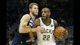 Milwaukee Bucks' Khris Middleton (22) drives to the basket against Minnesota Timberwolves' Jake Layman during the first half of a preseason NBA basketball game Thursday, Oct. 17, 2019, in Milwaukee. (AP Photo/Aaron Gash)