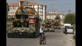 Children watch as army tanks are transported on trucks in the outskirts of the town of Akcakale, in Sanliurfa province, southeastern Turkey, at he border of Syria, Thursday, Oct. 17, 2019. U.S. Vice President Mike Pence, heading a delegation that includes Secretary of State Mike Pompeo and White House national security adviser Robert O'Brien, arrived in Turkey on Thursday, a day after Trump dismissed the very crisis he sent his aides on an emergency mission to douse.(AP Photo/Emrah Gurel)