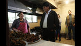 Bolivia's President Evo Morales, right, speaks with the cook during a visit to a trout farm where he stopped to eat, in Incachaca, Bolivia, Saturday, Oct. 19, 2019. Morales is seeking a fourth term in Sunday's general elections. (AP Photo/Juan Karita)
