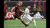 CORRECTS ID TO DEFENSEMAN JEFF LARENTOWICZ, NOT FORWARD HECTOR VILLALBA - Atlanta United defenseman Jeff Larentowicz, left, defends a kick by New England Revolution midfielder Carles Gil during the first half of an MLS Cup playoff soccer game Saturday, Oct. 19, 2019, in Atlanta. (AP Photo/John Amis)