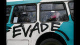 "People travel in a bus painted with graffiti that reads in Spanish ""Evade,"" in Santiago, Chile, Saturday, Oct. 19, 2019. Chile has been facing protests that started on Friday afternoon when high school students flooded subway stations, jumping turnstiles, dodging fares and vandalizing stations as part of protests against a fare hike, but by nightfall had extended throughout Santiago with students setting up barricades and fires at the entrances to subway stations, forcing President Sebastian Pinera to announce a state of emergency and deploy the armed forces into the streets. (AP Photo/Esteban Felix)"