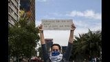 "A demonstrator raises a sign that reads in Spanish ""This is not for 30 pesos in fare, it's the drop that overflows the glass"" during a protest in Santiago, Chile, Saturday, Oct. 19, 2019. The protests started on Friday afternoon when high school students flooded subway stations, jumping turnstiles, dodging fares and vandalizing stations as part of protests against a fare hike, but by nightfall had extended throughout Santiago with students setting up barricades and fires at the entrances to subway stations, forcing President Sebastian Pinera to announce a state of emergency and deploy the armed forces into the streets. (AP Photo/Esteban Felix)"